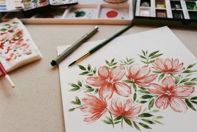 Pintando flores rojas. Papel, pincel y acuarelas sobre una mesa